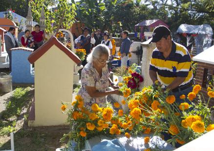 Acicalando arreglando una tumba con flores de cempoalxochitl