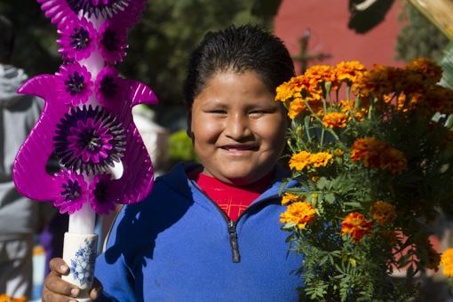 Niño con flores de cempoalxochitl y vela escamada